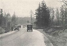 A black-and-white photograph of a paved road cutting through a wilderness-like scene. Four automobiles can be seen on the road, traveling in both directions, along with a man waiting on the shoulder.