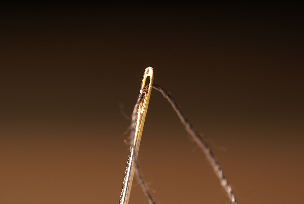 Sewing needle eye with thread