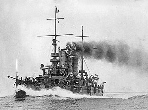 A small grey battleship traveling at full speed with smoke coming out of its two round funnels.