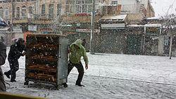 buy popular cc7f0 bd83b Two people pulling a cart of bread on Jaffa Street in Jerusalem, December  12, 2013