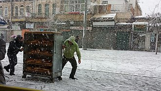 2013 Middle East cold snap - Two people pulling a cart of bread on Jaffa Street in Jerusalem, December 12, 2013