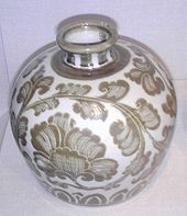 A handle-less jug which has a small bottom, a wide middle, and a very small opening at the top. The jug is white porcelain with a tan illustration of leaves or a vine wrapping around the entirety of the jug.