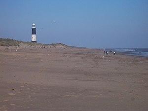 Plage sur la côte maritime du Spurn, avec le phare à l'horizon dans ...