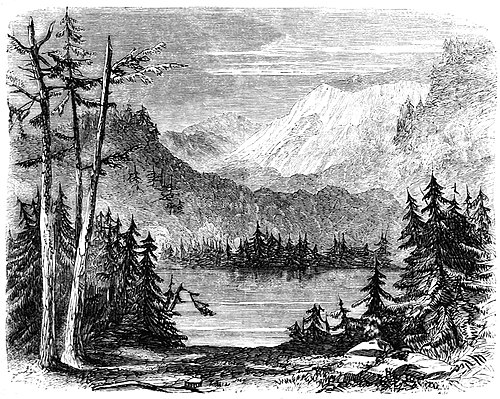 alt = A small lake, surrounded on every side by rocky shores, evergreen trees, and steep barren mountains. In the foreground, evergreen trees on both sides frame a glimpse of the lake; in the background are high peaks with snow on their tops.