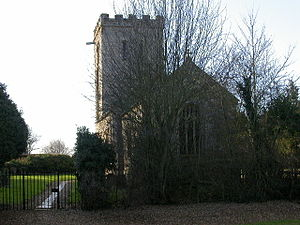 A stone church seen from the east, partly obscured by trees, with a battlemented parapet at the back