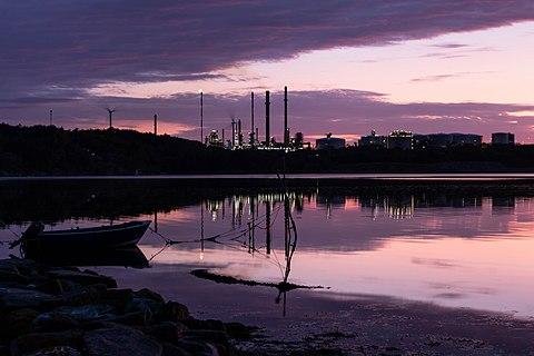 Sunset over Trommekilen, a part of Brofjorden, as seen from Norrkila, Lysekil Municipality, Sweden. In the background is Preemraff oil refinery.
