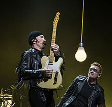 The Edge et Bono vêtus de vestes en cuir, comme The Edge tient une guitare à la verticale.  Une grande accroche ampoule ballants entre eux.