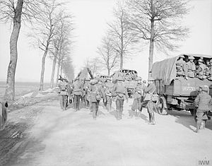 1st Guards Brigade (United Kingdom) - Stretcher bearers passing by motor lorries of the 2nd Battalion, Grenadier Guards, near Arras, France, 22 March 1918.