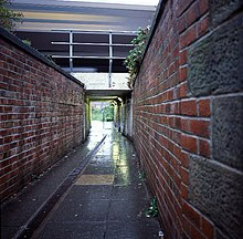 Narrow lane between two high brick walls leading to a tunnel under a railway bridge.