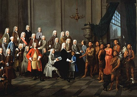 Yamacraw Creek Native Americans meet with the Trustee of the colony of Georgia in England, July 1734. The painting shows a Native American boy (in a blue coat) and woman (in a red dress) in European clothing. Tomo-chi-chi and other Yamacraws Native Americans.jpg