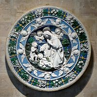A circular terracotta plaque, sculptured in relief and glazed in intense colours of blue and green with white figures and motifs. At the centre the Virgin Mary, watched by John the Baptist, kneels in adoration of the baby Jesus. Little cherubs look on