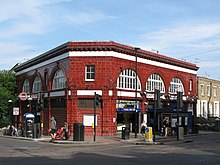 A two-storey station building in red glazed blocks sits at the corner of a road junction. Large semi-circular windows feature prominently on the upper floor.