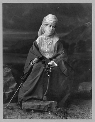 Turkish woman, full-length portrait, seated, facing front, holding parasol and flowers.jpg