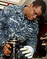 U.S. Navy Gunner's Mate 2nd Class DeAndre L. Edmondson greases a part for a .50-caliber machine gun mount in the armory aboard the aircraft carrier USS Nimitz (CVN 68) 130123-N-BJ752-072.jpg