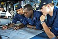 U.S. Navy Quartermaster 2nd Class Shaun Carlton, center, shows Quartermaster Seaman Christopher Carroll, right, and Boatswain's Mate 3rd Class Marshal Toone how to plot the ship's position on a chart aboard 130505-N-QL471-047.jpg