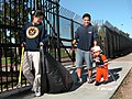 US Navy 041106-N-3581D-002 Engineman 2nd Class George Vidal and his family pick up trash outside 32nd Street Naval Station during the 11th annual Main Street Clean Up.jpg