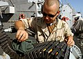 US Navy 050204-N-5345W-034 Gunner's Mate 3rd Class James Rutherford cleans the ammunition belt on a MK-38 25mm machine gun system he mans while standing port-side watch aboard the Arleigh Burke-class guided missile destroyer US.jpg