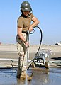 US Navy 071210-N-3857R-001 Engineering Aide Constructionman Devin Ahearn, of Naval Mobile Construction Battalion (NMCB) 1, uses a pressure washer to clean out the grooves of a pad of freshly placed concrete on a runway at Camp.jpg