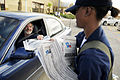 US Navy 080921-N-5758H-035 Hospital Corpsman Seaman Laketta Thomas, assigned to the amphibious assault ship USS Nassau (LHA 4), passes out copies of the local newspaper at a distribution point.jpg