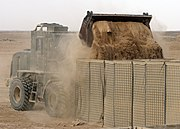US Navy 090411-N-8547M-011 A Seabee assigned to Naval Mobile Construction Battalion (NMCB) 5 uses an up-armored front end loader to fill HESCO barriers during a project at Camp Bastion