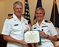 US Navy 090911-N-8273J-207 Chief of Naval Operations (CNO) Adm. Gary Roughead presents the Purple Heart medal to Cmdr. Kim LeBel for wounds received in action during her individual augmentee assignment in Afghanistan.jpg