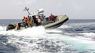 A Chief Master-at-Arms conducting RHIB training. US Navy 100818-N-9643W-129 Chief Master-at-Arms J. Del Omo, right, rides in a rigid-hull inflatable boat with sailors from the U.S. Navy and the Royal Barbados Defense Force.jpg