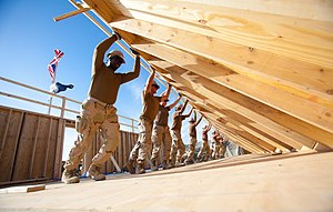 US Navy 101104-N-6383T-508 Seabees assigned to Naval Mobile Construction Battalion (NMCB) 18 erect an exterior wall for a Southwest Asian Hut at Ka.jpg