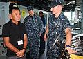 US Navy 110629-N-WL717-014 Ensign William Tessmann explains bridge equipment to Philippine Congressman Antonio Alvarez during a tour of the guided.jpg