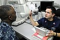 US Navy 110702-N-NB544-021 Hospital Corpsman 2nd Class Luis Garcia, from Phoenix, conducts an eye exam aboard the aircraft carrier USS Ronald Reaga.jpg