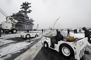 US Navy 120120-N-HN953-015 Sailors aboard the aircraft carrier USS Nimitz (CVN 68) remove snow from the ship's flight deck.jpg