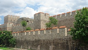 Walls of Constantinople - Restored section of the Theodosian Walls at the Selymbria Gate. The Outer Wall and the wall of the moat are visible, with a tower of the Inner Wall in the background.