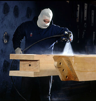 Wood finishing - A worker sprays a urethane finish onto a timber
