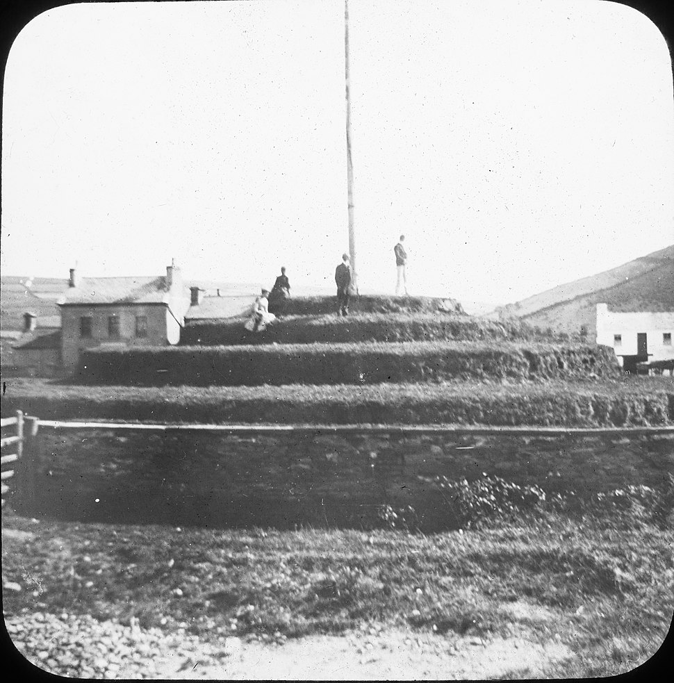 """Turnwake, with figures at base of flagpole"" - is Tynwald Hill, Isle of Man (26966343094)"