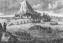 Two whaleboats beached in foreground, 5 rowed and 4 sailing whaleboats chasing/attacking 5 whales, two larger whaling ships nearby, and sun peeking around snow-covered mountain in background