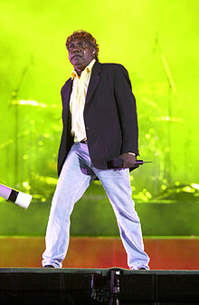 A 44-year-old man is standing upon a stage. He wears light blue jeans, a black unbuttoned jacket, a yellow shirt and a head band. He holds a portable microphone in his left hand at his side and is staring ahead. Behind him is band equipment or a screen lit up in a green display.