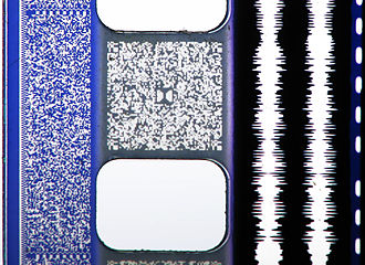"Sony Dynamic Digital Sound - A photo of a 35 mm film print featuring all four audio formats (or ""quad track"")- from left to right: SDDS (blue area to the left of the sprocket holes), Dolby Digital (grey area between the sprocket holes labelled with the Dolby ""Double-D"" logo in the middle), analog optical sound (the two white lines to the right of the sprocket holes), and the DTS time code (the dashed line to the far right.)"