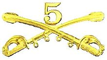 A computer generated reproduction of the insignia of the Union Army 5th Regiment cavalry. The insignia is displayed in gold and consists of two sheafed swords crossing over each other at a 45 degree angle pointing upwards with a Roman numeral