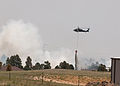 A pilot of a UH-60 Black Hawk helicopter assigned to the 4th Combat Aviation Brigade, 4th Infantry Division, spreads water out of a helicopter bucket from a local pond to be dispersed on the Black Forest fire 130613-A-UK001-311.jpg