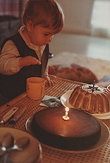 a young child preparing to extinguish the candle of his first birthday 1983