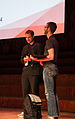 Aaron Halfaker conversing with a member of the press at Wikimania 2014.jpg