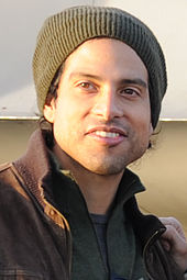 An image of a man wearing a jacket and a hat looking toward the camera.