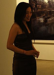 A long-haired East Asian woman in a black dress