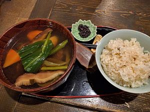 Ainu cuisine - An Ainu-style meal with venison and mountain vegetable soup (yuk ohaw), fermented salmon liver (mefun) and rice mixed with grains.