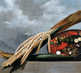 Still-life of flowering coconut palm, nuts and red pepers