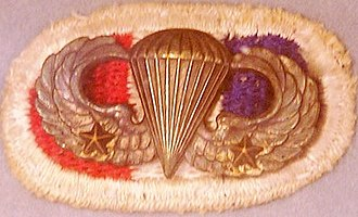 Parachutist Badge (United States) - Basic Parachutist Badge of a World War II veteran from the 506th Parachute Infantry Regiment, 101st Airborne Division (as indicated by the background trimming) who made two combat jumps (as indicated by the two Combat Jump Devices).