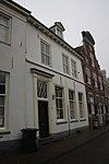 foto van Witgepleisterd woonhuis met rechte kroonlijst. Houten deuromlijsting