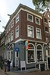 foto van Hoekhuis onder schilddak met gepleisterde omlopende pui, waarin rondboogvensters onder lijst