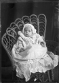 An unidentified infant seated in a cane chair ATLIB 330186.png