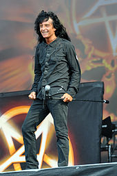 Smiling, casually-dressed singer with long, black hair onstage