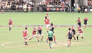 Australian rules football in Australia - An Australian Football League match at Carrara Stadium on the Gold Coast. Adelaide's Matthew Clarke and Melbourne's Mark Jamar contest a centre bounce. The man in the green shirt is a central field umpire.